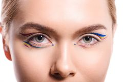 cropped image of woman with colored makeup with lines looking at camera stock image