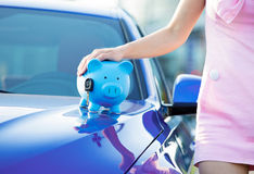 Cropped image woman customer, new car, piggy bank, key. Cropped image woman customer, agent and new car, piggy bank, key on hood, isolated outside, outdoors stock photos