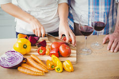 Cropped image of woman cutting tomatoes with husband Stock Photos