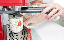Cropped image of woman dispensing coffee from machine in kitchen. Cropped image of women dispensing coffee from machine in kitchen Stock Photos