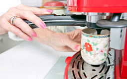Cropped image of woman dispensing coffee from machine in kitchen Royalty Free Stock Images