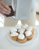 Cropped image of woman grating chocolate on cupcakes at counter Stock Photo