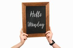 Cropped image of woman hands holding chalkboard with lettering hello monday on white stock image