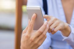 Cropped image woman hands holding, using smartphone. Closeup image woman hands holding, using smart, mobile phone isolated outside city background. New royalty free stock photos