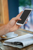 Cropped image of woman holding mobile phone at table Stock Photo