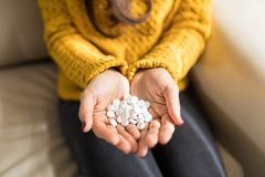 Woman With Prescribed Medicines. Cropped image of woman holding white tablets in cupped hands at home stock image