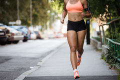 Cropped image of a woman jogger on sidewalk, wearing armband. Stock Photos