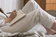 Cropped image of a woman in pajamas lying in bed and is a piece of desire. Side view Royalty Free Stock Image