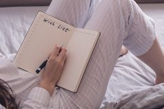 Cropped image of a woman in pajamas lying in bed and is a piece of desire. Rear view Stock Image