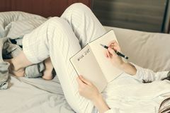 Cropped image of a woman in pajamas lying in bed and is a piece of desire. Toned Stock Photo