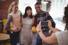 Cropped image of woman photographing friends from smartphone. Cropped image of women photographing friends from smartphone at coffee shop Stock Image