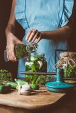 cropped image of woman preparing preserved cucumbers and pouring water into jar royalty free stock image