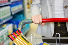 Cropped image of woman pushing trolley in aisle Royalty Free Stock Photo
