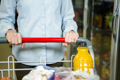 Cropped image of woman pushing trolley in aisle Stock Image