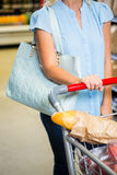 Cropped image of woman pushing trolley in aisle Royalty Free Stock Photos