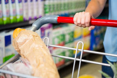 Cropped image of woman pushing trolley in aisle Royalty Free Stock Images