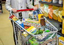 Cropped image of woman pushing trolley. In supermarket Stock Photo