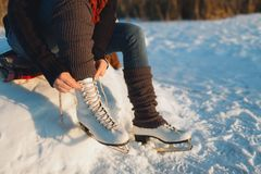 Woman lacing ice skates at the edge of a frozen lake Royalty Free Stock Images