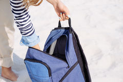 Cropped image: woman's hands opened the blue backpack and pulled Stock Photography