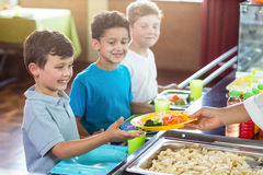 Cropped image of woman serving food to children Stock Images