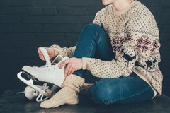 Woman sitting on gray floor and wearing white skates Stock Photography