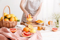 Cropped image of woman squeezes out juice of a citruses. Royalty Free Stock Images