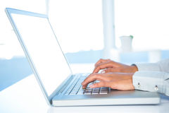 Cropped image of woman using laptop Stock Images