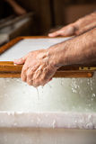 Cropped Image Of Worker Dipping Mold In Mixture Royalty Free Stock Image