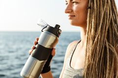 Cropped image of young athlete woman. Standing at the beach and drinking water from a bottle royalty free stock images