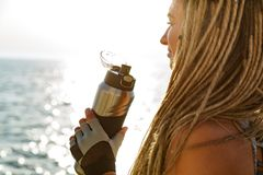 Cropped image of young athlete woman. Standing at the beach and drinking water from a bottle royalty free stock photo