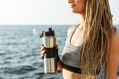 Cropped image of young athlete woman. Standing at the beach and holding water bottle stock photography