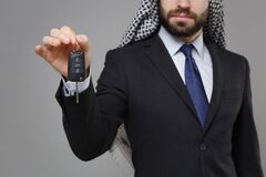 Cropped image of young bearded arabian muslim businessman in keffiyeh kafiya ring igal agal classic black suit