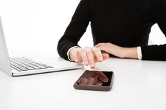 Cropped image of young business lady using laptop and phone. Royalty Free Stock Photo