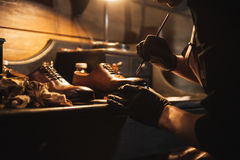 Cropped image of young concentrated man shoemaker. At footwear workshop stock photography