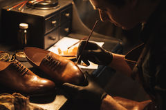 Cropped image of young concentrated man shoemaker. At footwear workshop stock photos
