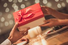 Couple celebrating New Year. Cropped image of young couple holding a gift box while celebrating New Year in a restaurant Royalty Free Stock Photo