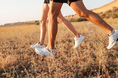 Cropped image of a young couple legs in sneakers running Royalty Free Stock Image