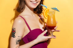 Cropped image of a young girl in swimsuit holding cocktail Stock Photo