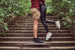 Cropped image of young hipster couple, cuddling while standing on steps in a park. Royalty Free Stock Photos