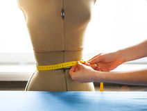 Cropped image of young male tailor measuring mannequin`s waist i. N fashion studio, dummy close up Stock Photos