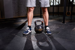 Cropped image of young man, legs in shorts and kettlebell. Crossfit workout theme on grey background. Stock Photo