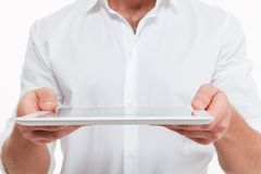 Cropped image of young man give you a tablet computer. Cropped image of young man standing over white wall background isolated. Give you a tablet computer Royalty Free Stock Photography