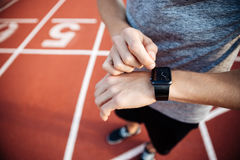 Cropped image of a young muscular man adjusting smart watch Royalty Free Stock Photo