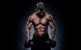 Cropped image of young muscular man doing heavy dumbbell exercis Royalty Free Stock Photos