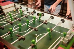 Cropped image of young people playing table soccer resting outdoors royalty free stock photography