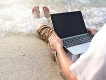 Cropped image of young relaxed man with laptop sitting on the sandy beach with soft waves. Internet of things concept. Cropped image of young relaxed man with royalty free stock photography