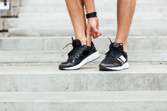Cropped image of young sports man footwear. At the stadium outdoors Stock Image