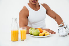Cropped image of young sportsman near fruits. royalty free stock photography