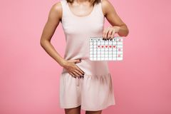 Cropped image of a young woman in dress. Holding periods calendar and touching her belly isolated over pink background Royalty Free Stock Photos
