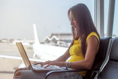 Cropped image of young woman holding a laptop on lap typing keyboard indoors in public place. Cropped image of young woman holding a laptop on lap typing on stock image